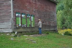 man looking at sign on barn