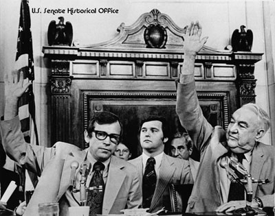 Senators Howard Baker (R-TN) and Sam Ervin (D-NC) cast votes during the Senate Watergate Committee hearings of 1973. Seated behind the senators is the ...
