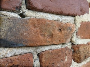 This handprint on one of the bricks of the wall surrounding the old campus was very likely made by a slave.  Photo:  Slavery at South Carolina College team.