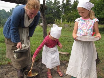 Young visitors to the National Colonial Farm learn the colonial skill of making apple butter from bruised apples. This weekend Green History programming is paired with a current-day exhibit about the problem of food waste (another contributor to global warming). Photo courtesy of the author.