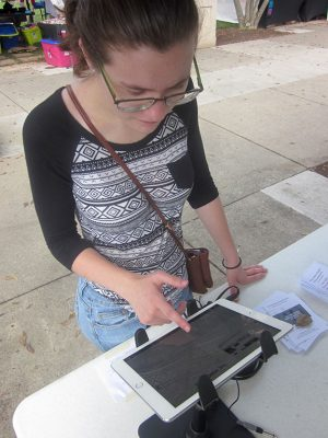 Roanoke College Work-Study Research Assistant Haleigh Ardolino tests out the technology for presentation of a digital exhibition at the Southwest Virginia LGBTQ+ History Project's booth at the Pride in the Park festival, September 11, 2016. Photo credit: Photograph by the author.
