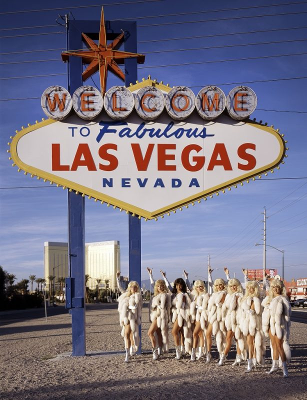 Eight women dressed in showgirl costumes stand under and gesture up to Las Vegas sign.