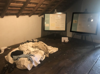 A view of the exhibit in the loft space of the historic Wentz house, including exhibit panels and hands-on objects (such as reproduction clothing). Image courtesy of Montgomery County- Division of Park, Trails, & Historic Sites- April 2019.