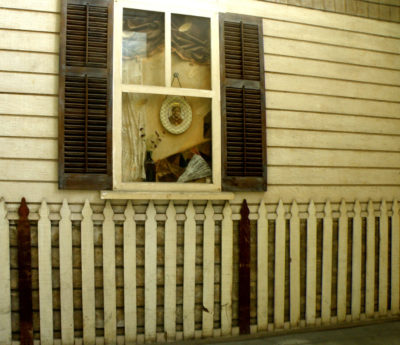 This is a photograph of the house facade of the Biddy Mason memorial. It includes siding, a fence, and a window with a portrait and other domestic items.