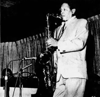 This is a black and white photograph of an African American man playing a saxophone in 1965. He is inside a club. There is stage equipment and a curtain in the background.