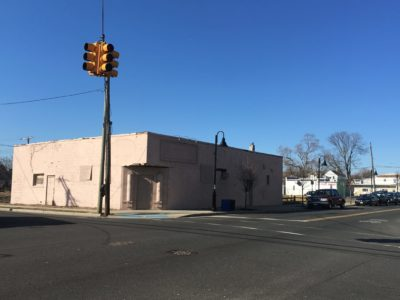 This is a photograph of a being building on a corner (the Turf Club). It is shuttered. There is a streetlight in the foreground, and there are cars parking at right. The photograph was taken in 2018.