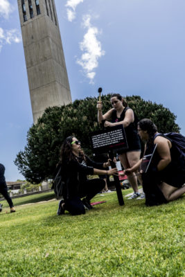 Three students work together to pound sign with testimony into the lawn in front of Storke Tower on the UCSB campus. Photo credit: Bennett Barthelemy