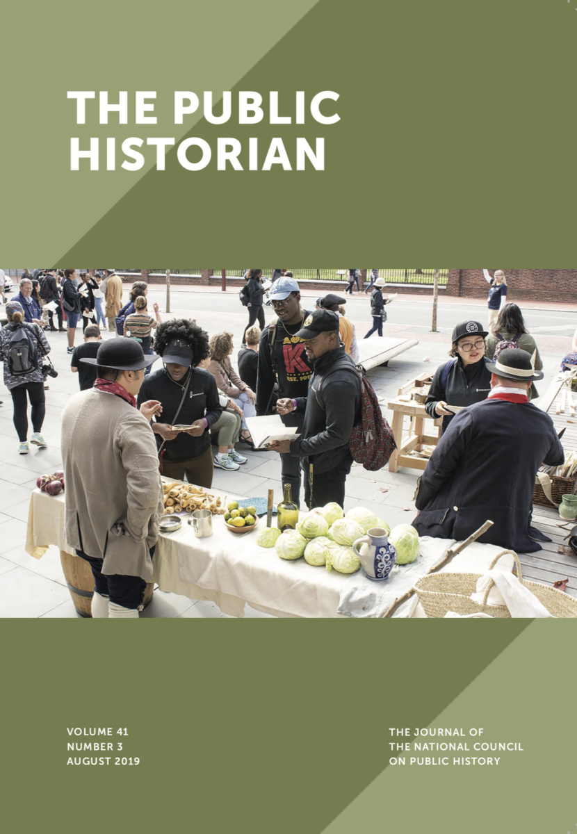 This image is a detail of the cover of the 41.3 (August 2019) issue of The Public Historian. The cover features a green ground and a photograph of costumed interpreters speaking with the public outside. The interpreters are wearing eighteenth-century dress and are surrounded by produce such as cabbage and limes.