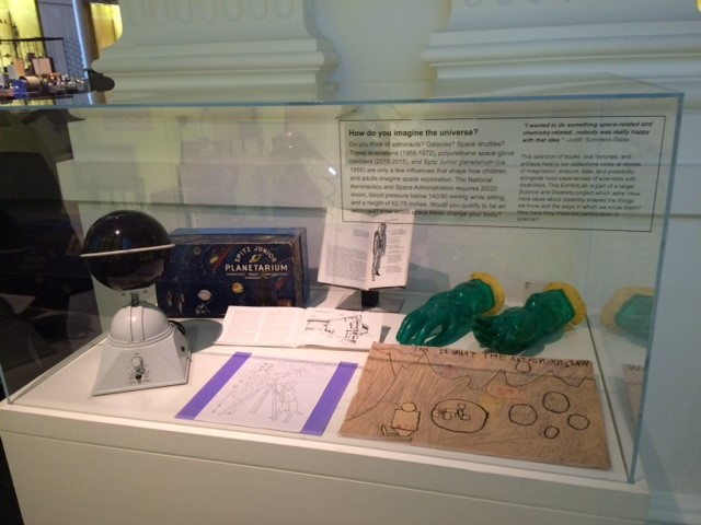 An exhibition case with seven objects, including a model planetarium, a box for the planetarium, gloves, a pamphlet, a drawing, and two documents.