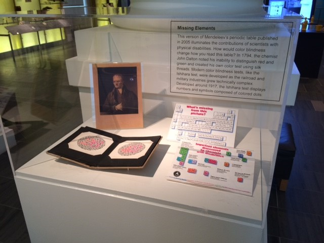 Details of exhibition case with four objects, Close up of exhibition case with four objects, including a portrait of chemist John Dalton, the color-blindness chart John Dalton invented, a raised periodic table, and elements discovered by scientists with disabilities. The exhibition label is in the background of the case