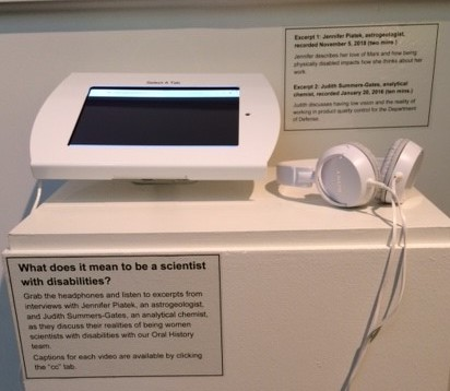 A device on which a person can watch a video interview and headphones rest on a platform. There is an exhibition label on the platform explaining that you can listen to interviews with two women scientists describe their experiences as women scientists with disabilities.