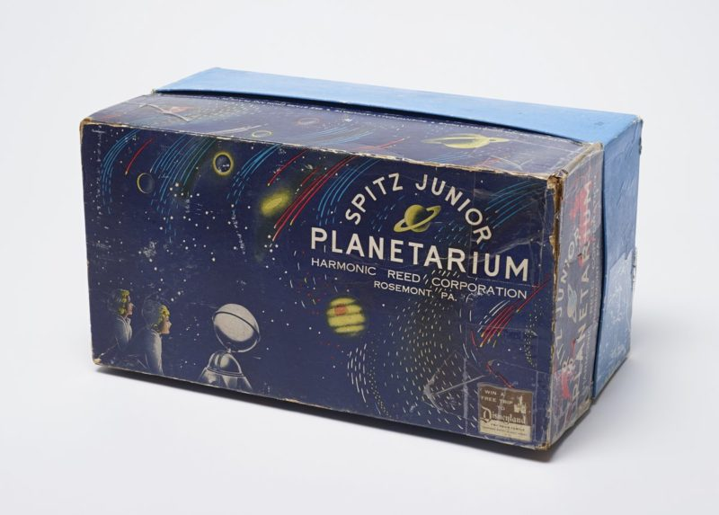 A box features a white boy and girl in the lower left hand corner, a planetarium, and the name of the toy. The box is decorated with images of planets, comets, and stars.