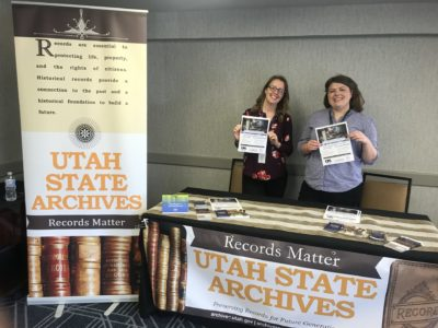 """This is a color photograph of two smiling people holding flyers and standing behind a table decorated with a banner that says """"Records Matter/Utah State Archives."""" There is also a vertical banner at left that adds: """"Records are essential to protecting life, property, and the rights of citizens. Historical records provide a connection to the past and a historical foundation to build a future."""""""