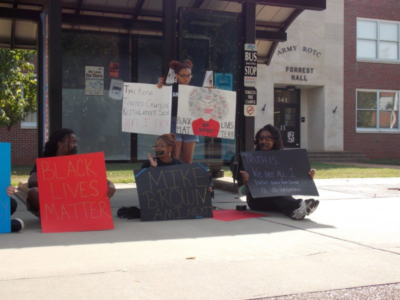 "In this color photograph, four African American students holding signs with messages on them such as ""Black Lives Matter"" are sitting and standing. There is a building in the background labeled ""ARMY ROTC/FORREST HALL."""